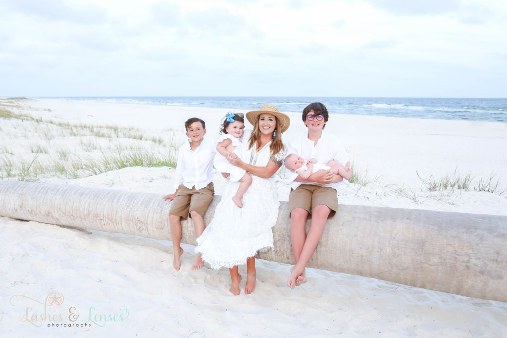 Mom with her three sons and daughter sitting on a washed up palm tree on the beach at Johnsons Beach in Perdido Key Florida