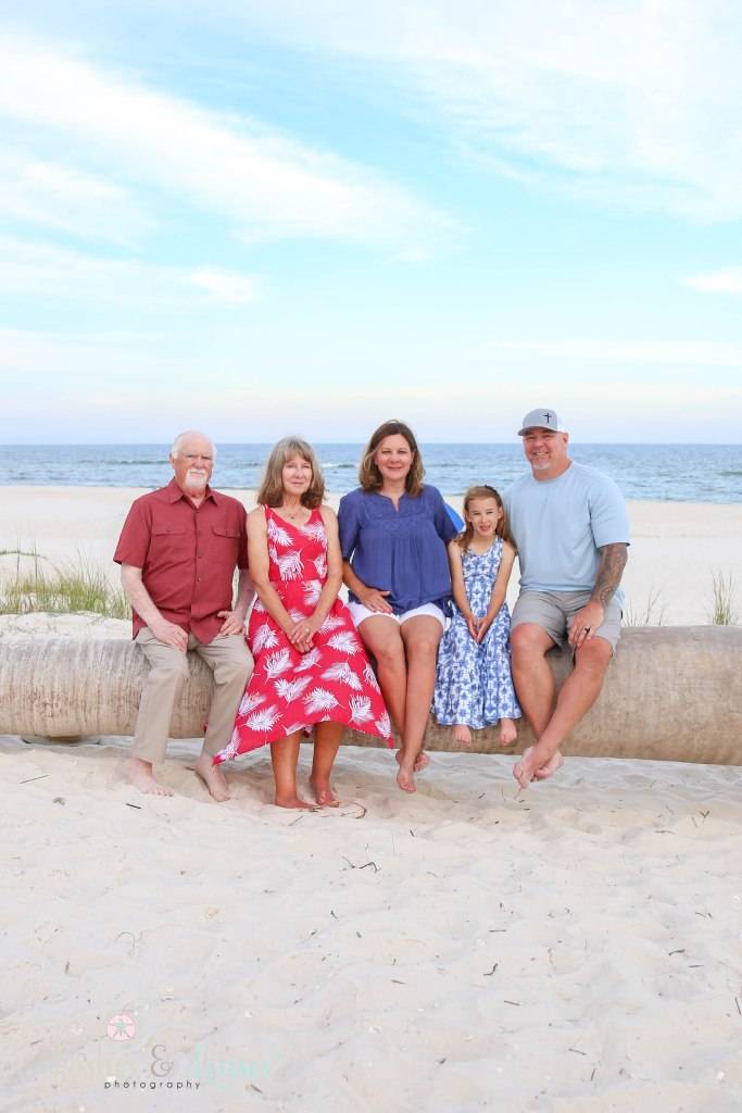 Grandparents, Mom and Dad and granddaughter sitting on a washed up palm tree on the beach at Johnsons Beach in Perdido Key Florida
