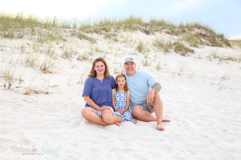 Mom and Dad with elementary age daughter sitting in the sand next to the sand dunes at Johnsons Beach in Perdido Key Florida