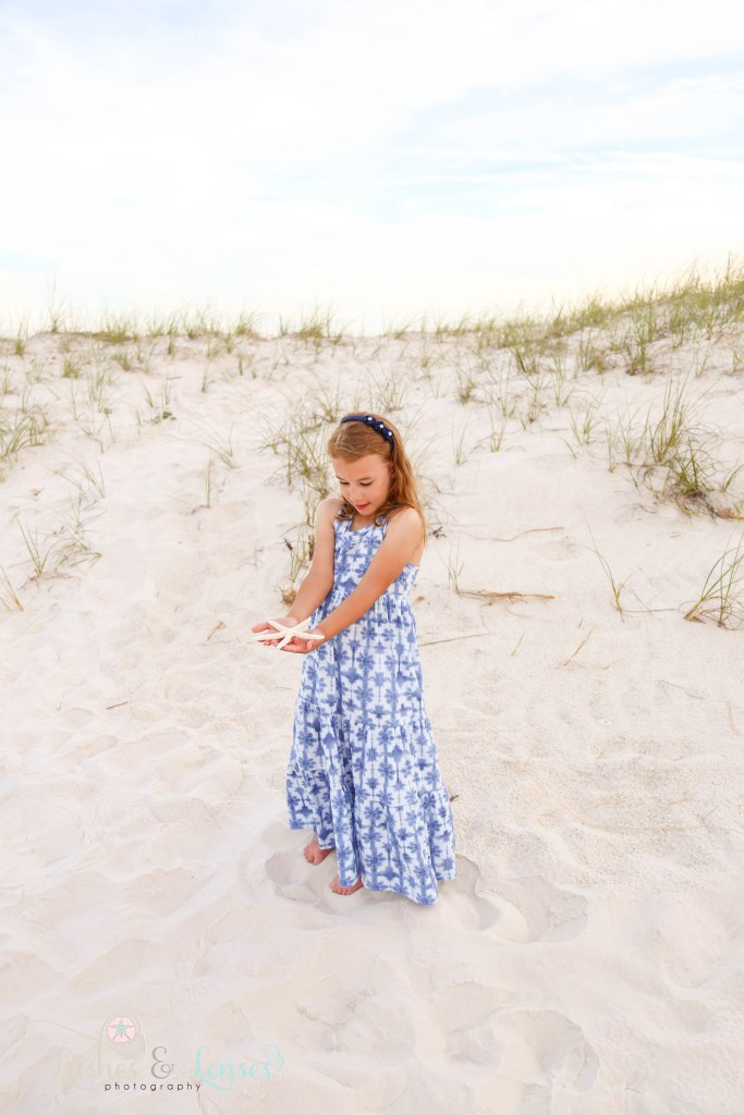 Young girl holding a starfish in her hands and looking at it at Johnsons Beach in Perdido Key Florida