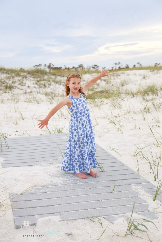 Little girl doing a ballet pose on the boardwalk at Johnsons Beach in Perdido Key Florida