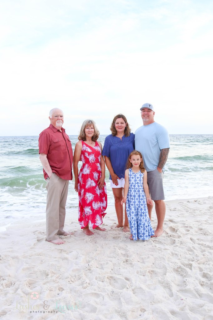 Family consisting of grandparents, parents and daughter standing by the water at Johnsons Beach in Perdido Key Florida