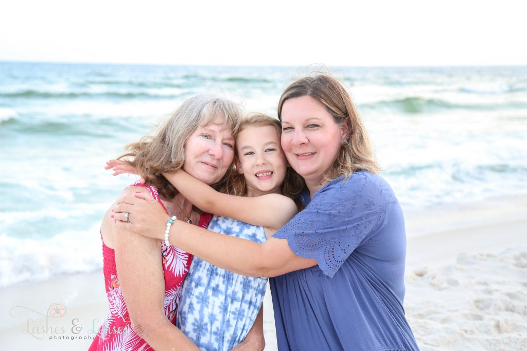Grandma, Mom and Granddaughter hugging each other next to the water at Johnsons Beach in Perdido Key Florida