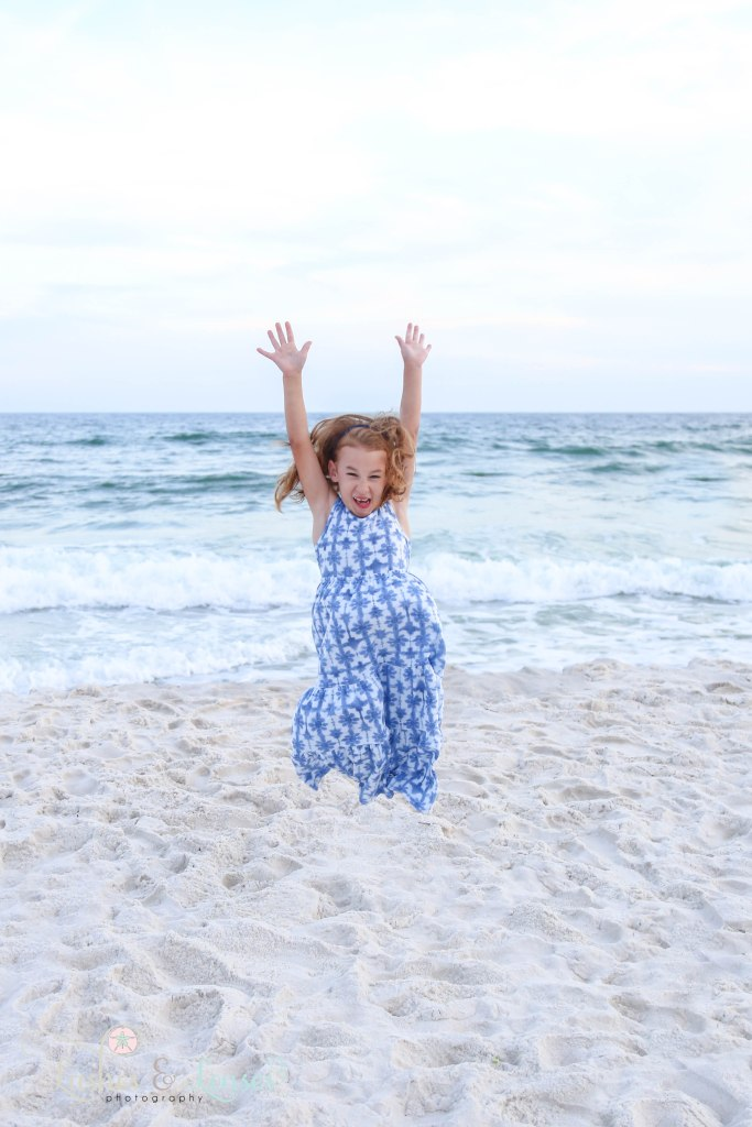 Young girl jumping for joy at the waters edge at Johnsons Beach in Perdido Key Florida