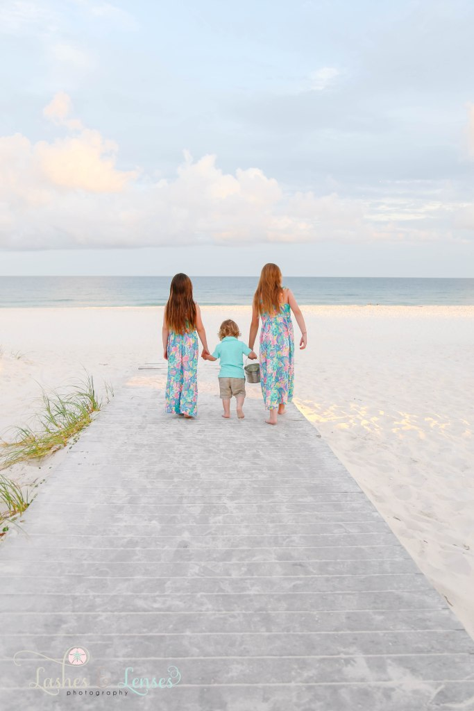 Two older sisters holding their toddler brother's hand and walking down the boardwalk towards the water at Johnsons Beach in Perdido Key Florida