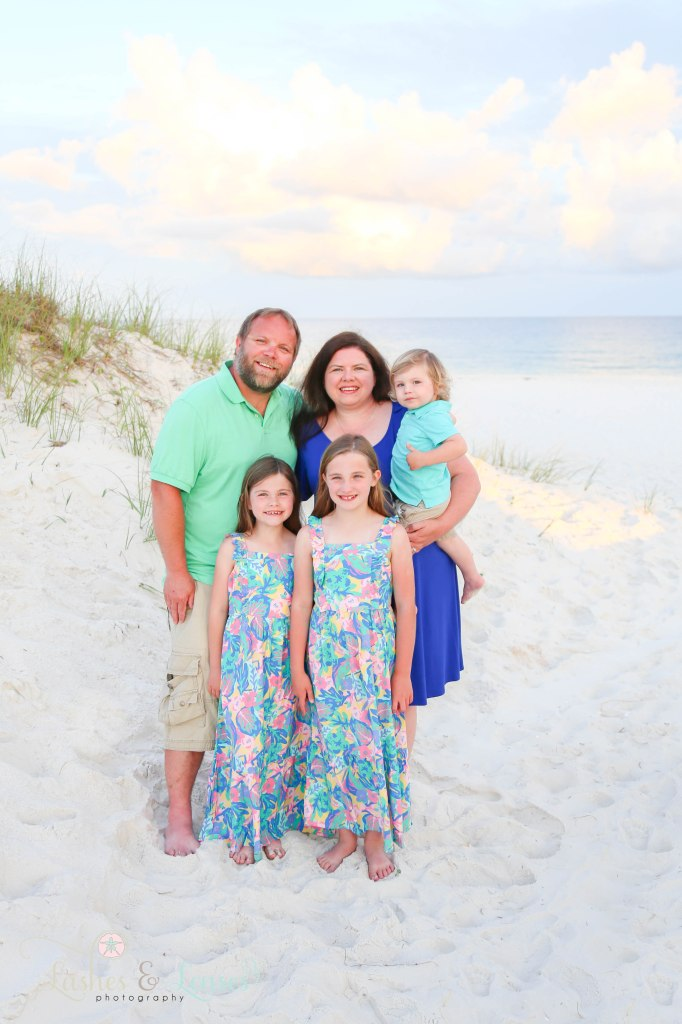 Mom and Dad standing with their two daughters and son next to the sand dunes with the water behind them at Johnsons Beach in Perdido Key Florida