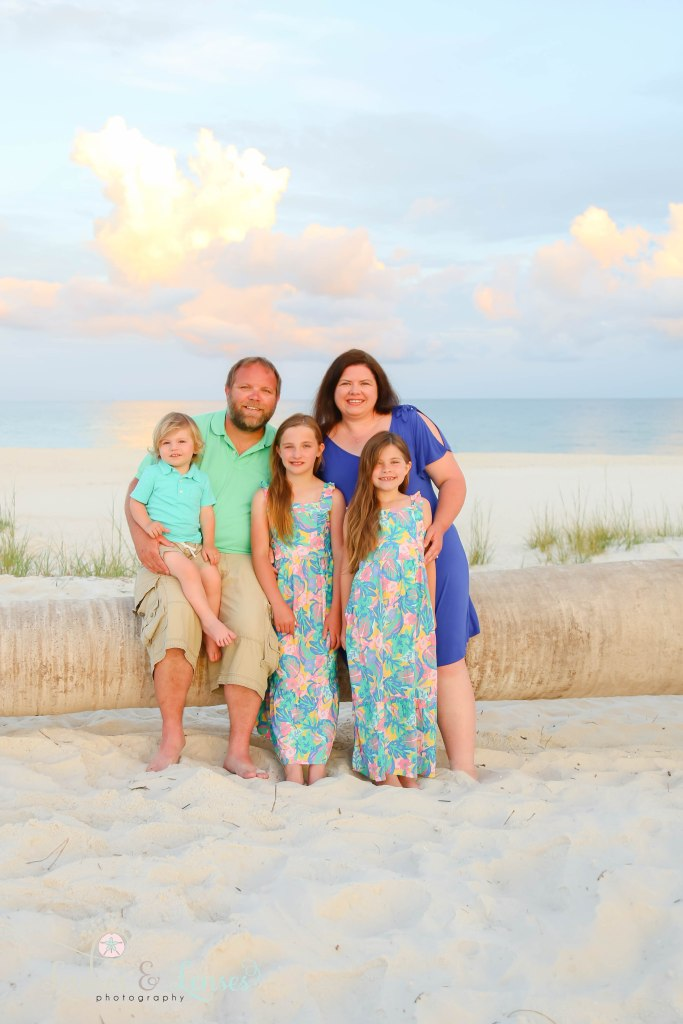 Family of five sitting on a washed up palm tree on the beach with the water behind them at Johnsons Beach in Perdido Key Florida