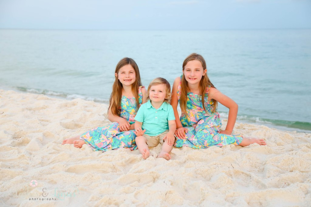 Two sisters and brother sitting at the waters edge at Johnsons Beach in Perdido Key Florida