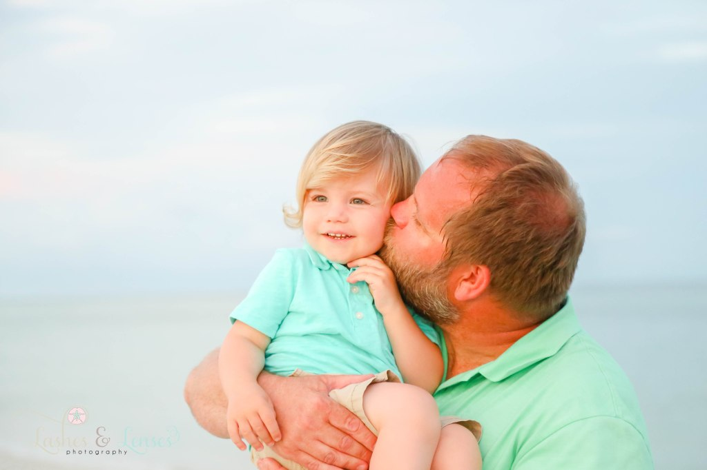Dad kissing his toddler son on the cheek with the gulf waters behind them at Johnsons Beach in Perdido Key Florida