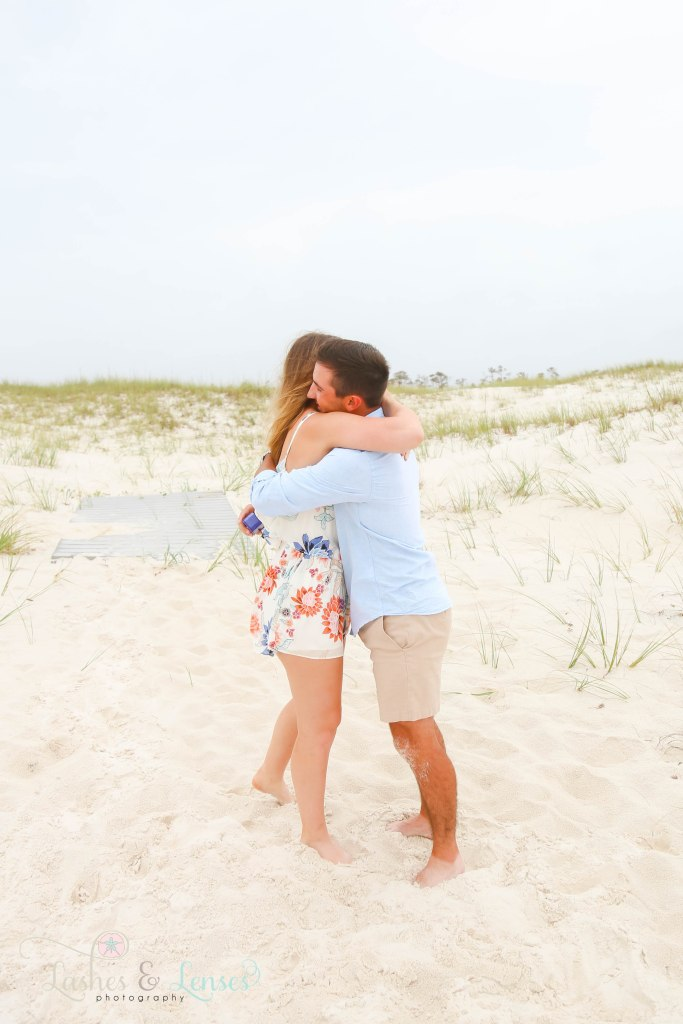 Surprise Engagement Session, newly engaged couple hugging with the sand dunes behind them at Johnsons Beach in Perdido Key Florida