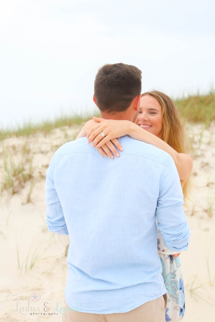 Surprise Engagement Session, young woman with her arms around her new fiancés neck showing off ring at Johnsons Beach in Perdido Key Florida
