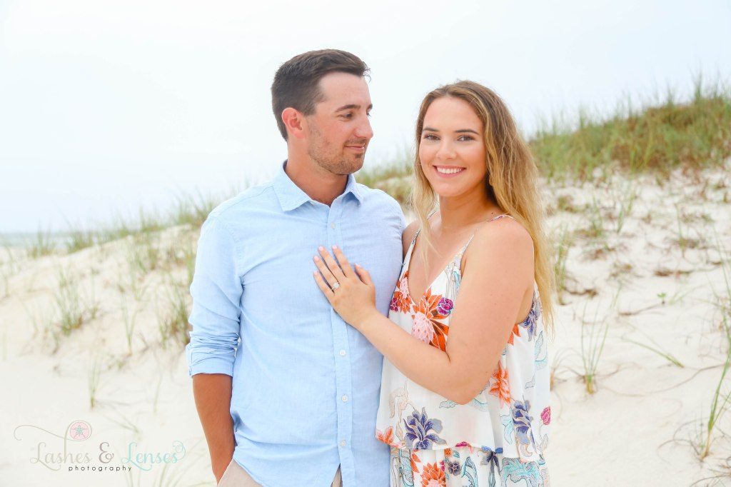 Surprise Engagement Session, young woman looking at the camera with her hand on her fiancé's chest and young man looking at his new fiancé at Johnsons Beach in Perdido Key Florida