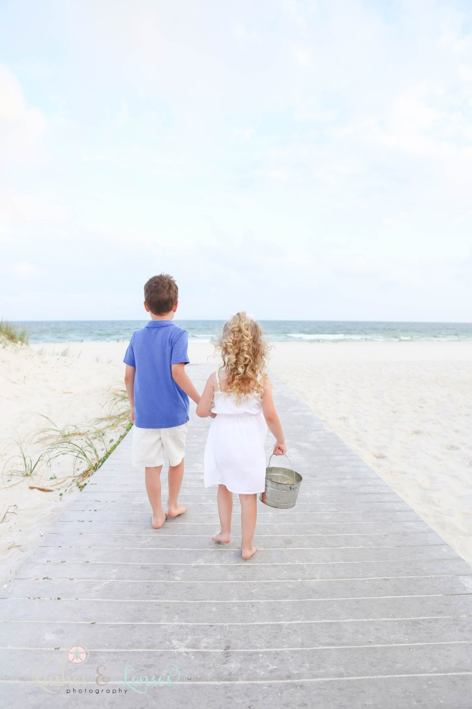Young brother and sister holding hands and walking down the boardwalk towards the water at Johnsons Beach in Perdido Key Florida
