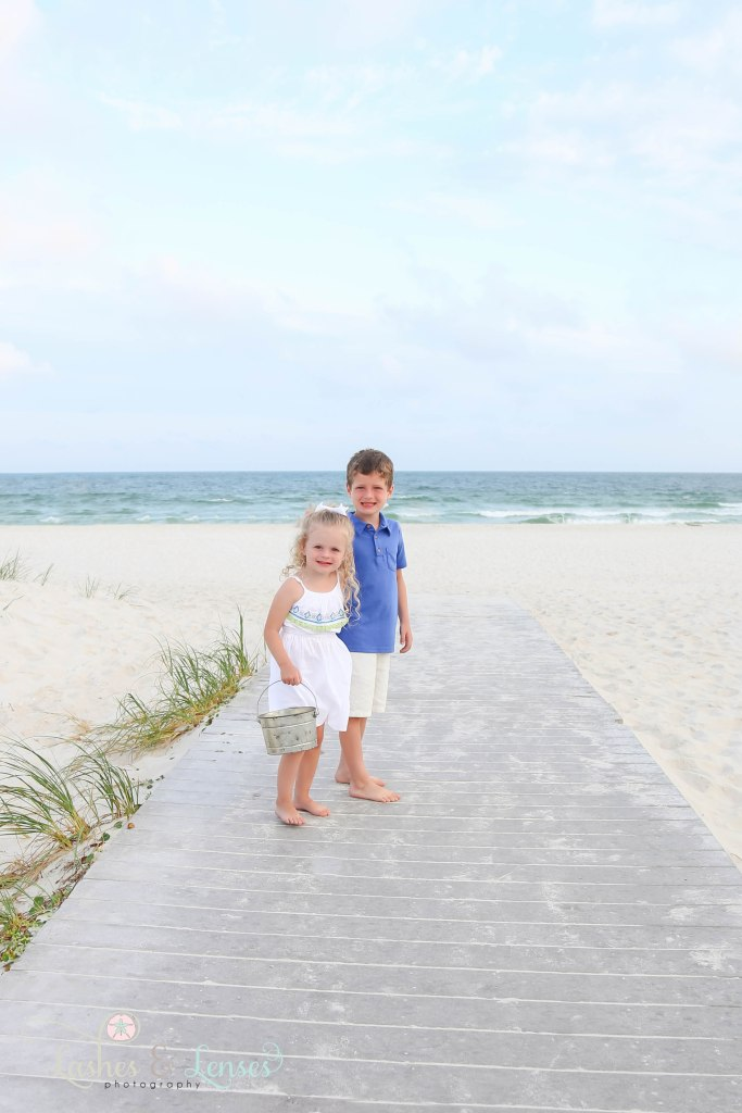 Young brother and sister holding hands and walking down the boardwalk, looking at the camera at Johnsons Beach in Perdido Key Florida