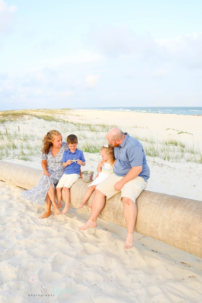 Mom and Dad sitting on a washed up palm tree with their son and daughter sitting next to them at Johnsons Beach in Perdido Key Florida