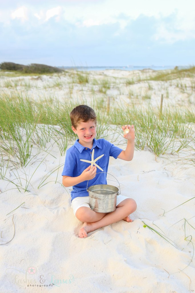 Elementary age boy sitting in the sand and showing off his seashells at Johnsons Beach in Perdido Key Florida