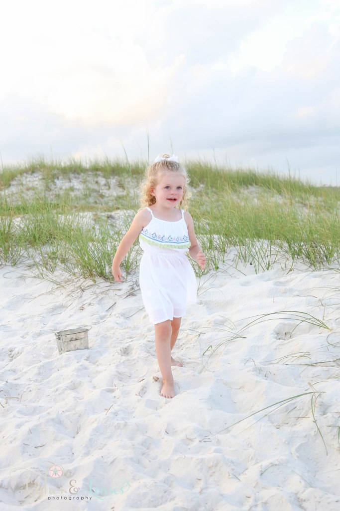 Toddler girl smiling and looking off camera with her sand bucket behind her at Johnsons Beach in Perdido Key Florida