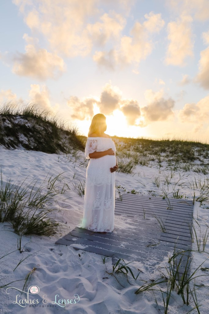 Beautiful maternity photo, woman holding her belly with a sun flare behind her at Johnsons Beach in Perdido Key Florida