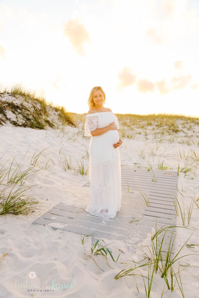 Pregnant woman holding her belly and smiling at the camera at Johnsons Beach in Perdido Key Florida