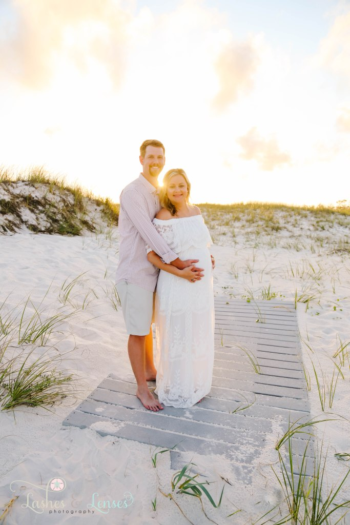 Husband hugging wife and holding her belly with the sunset behind them at Johnsons Beach in Perdido Key Florida