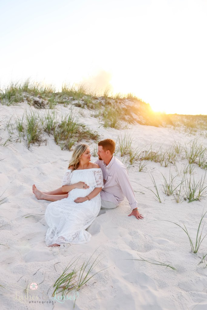 Husband and wife sitting in the sand and looking at each other, woman is holding her belly at Johnsons Beach in Perdido Key Florida