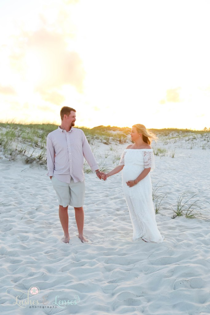 Husband and wife getting ready to walk down the beach and holding hands at Johnsons Beach in Perdido Key Florida