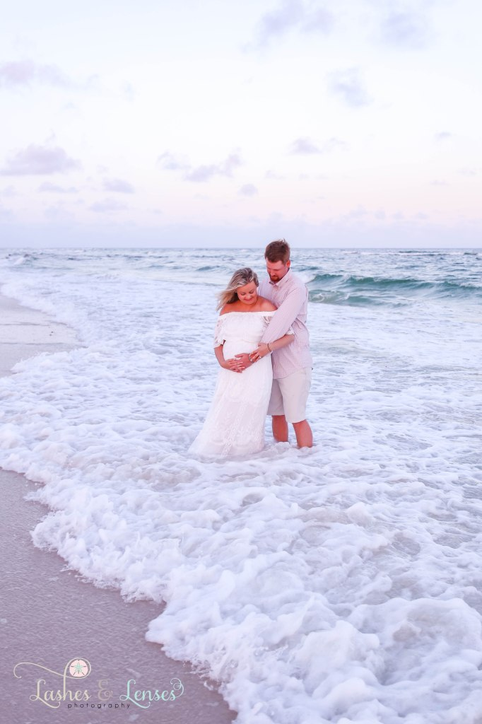 Pregnant couple standing in the water cradling moms belly at Johnsons Beach in Perdido Key Florida