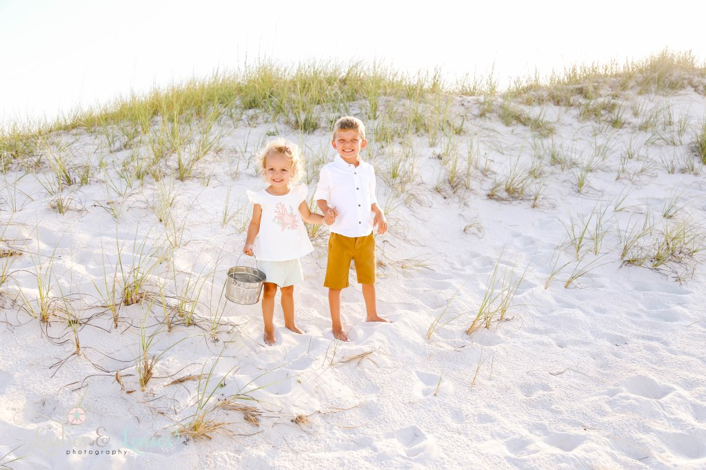 Brother and Sister holding hands next to the sand dunes at Johnsons Beach in Perdido Key Florida
