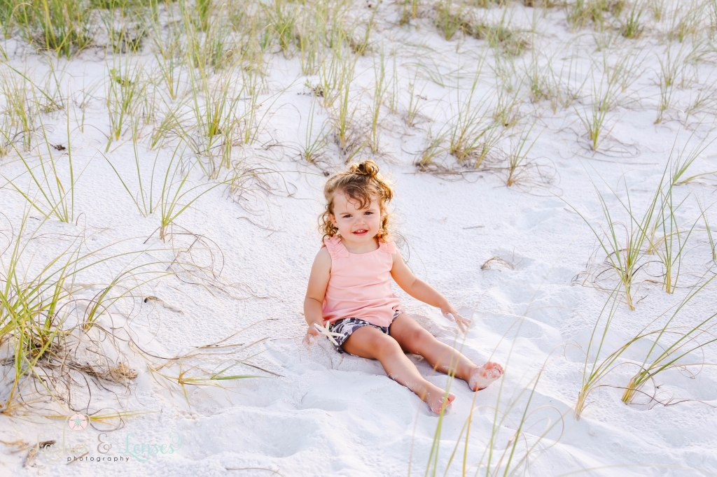 Toddler girl sitting in the sand with sea grass behind her and holding a starfish at Johnsons Beach in Perdido Key Florida