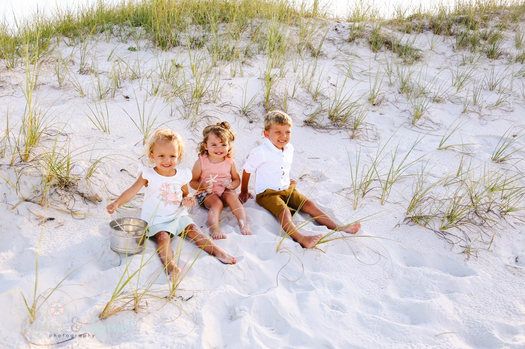 Cousins sitting in the sand with sea grass behind them at Johnsons Beach in Perdido Key Florida