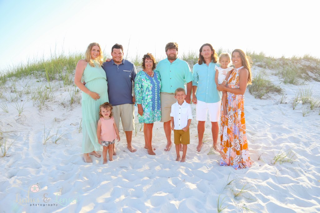 Extended family including grandparents two sets of children and grandchildren standing in the sand at Johnsons Beach in Perdido Key Florida