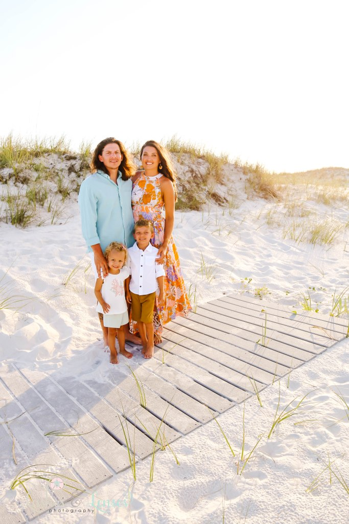 Mom and Dad standing with their son and daughter on the boardwalk at Johnsons Beach in Perdido Key Florida