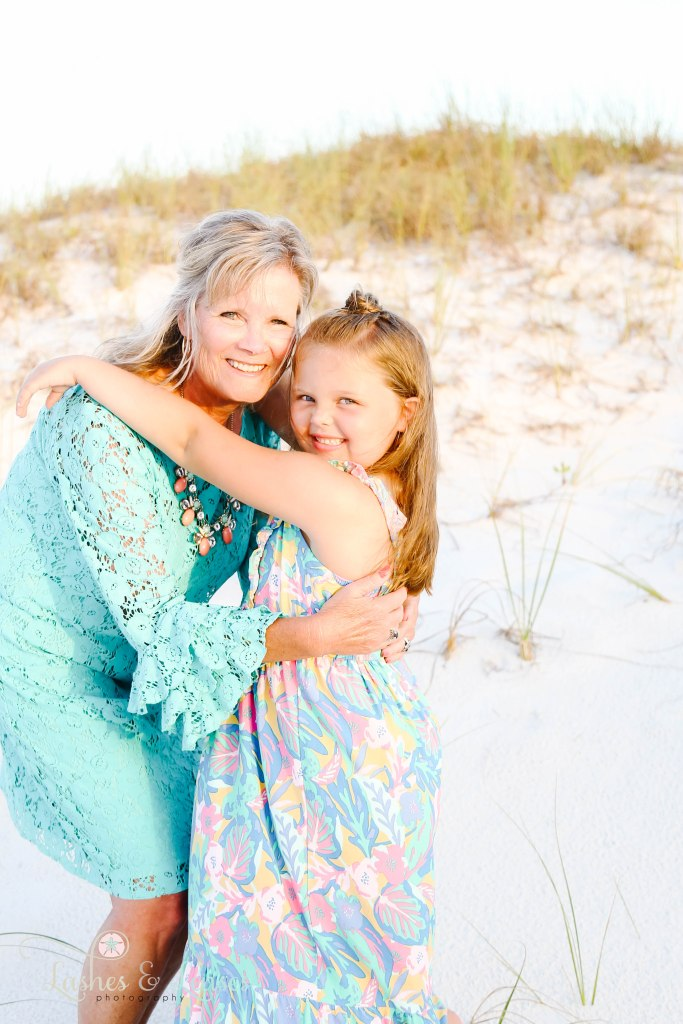 Grandma and granddaughter hugging with the sun-shining on their hair at Johnsons Beach in Perdido Key Florida