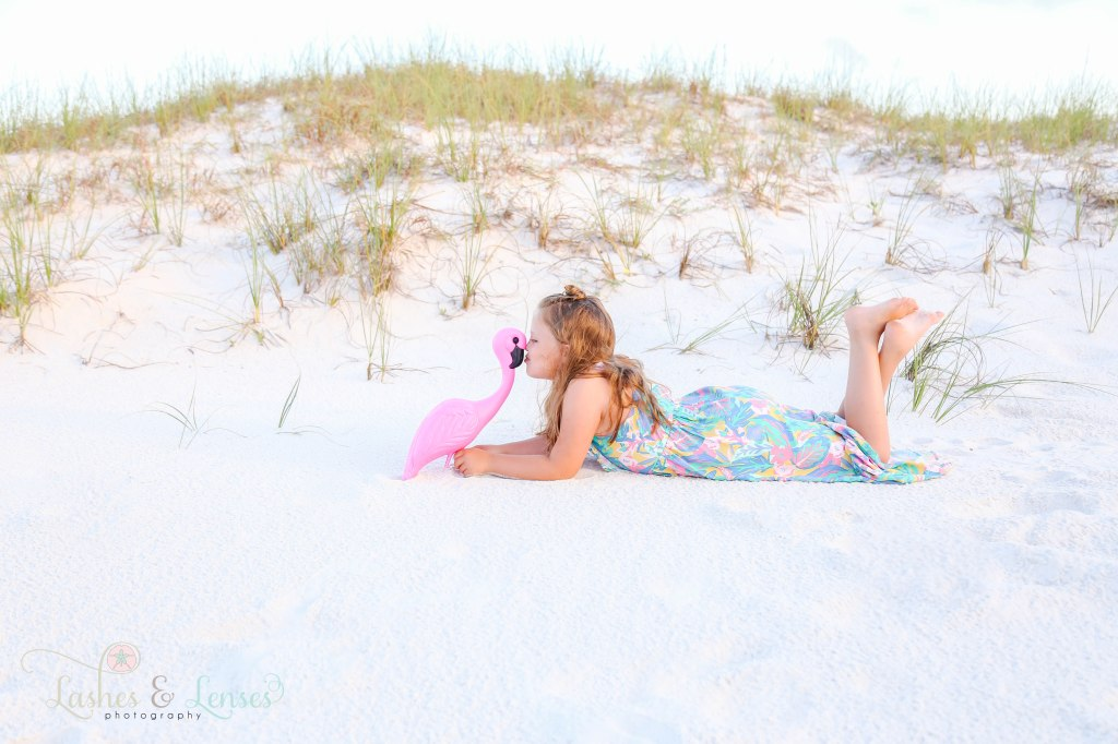 Young girl laying on her belly with her feet in the air, kissing a plastic pink flamingo at Johnsons Beach in Perdido Key Florida