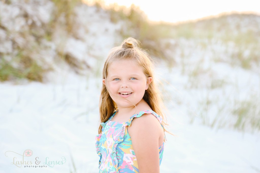 Young girl standing with the sand dunes behind her and the sunset at Johnsons Beach in Perdido Key Florida