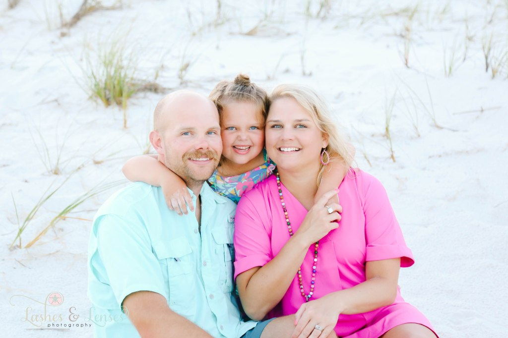 Mom and Dad sitting on the ground with their daughter hugging them from behind at Johnsons Beach in Perdido Key Florida