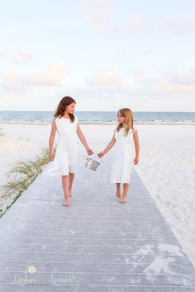 Sisters walking down the boardwalk and holding a sand bucket with the water behind them at Johnsons Beach in Perdido Key Florida