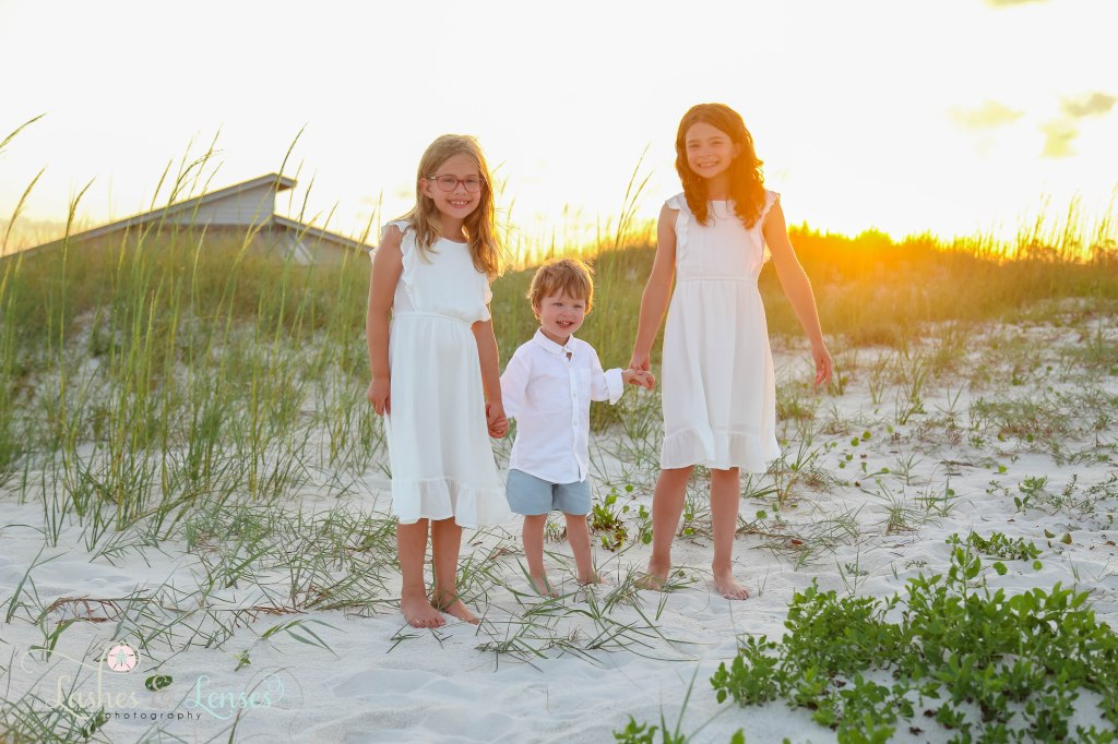 Two sisters with toddler cousin standing next to the sand dunes with the sunset behind them at Johnsons Beach in Perdido Key Florida