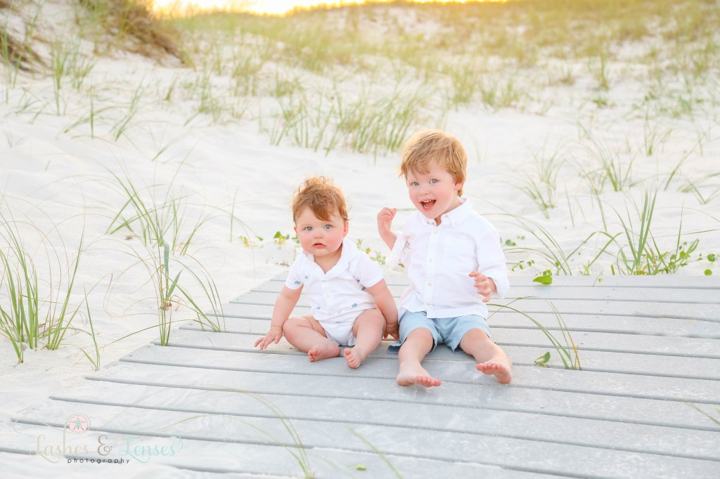 Two young brothers sitting on a washed up boardwalk with the sunset behind them at Johnsons Beach in Perdido Key Florida