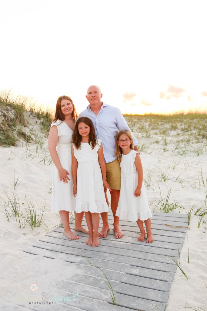Mom and Dad with their two preteen daughters standing on the boardwalk with the sunset behind them at Johnsons Beach in Perdido Key Florida