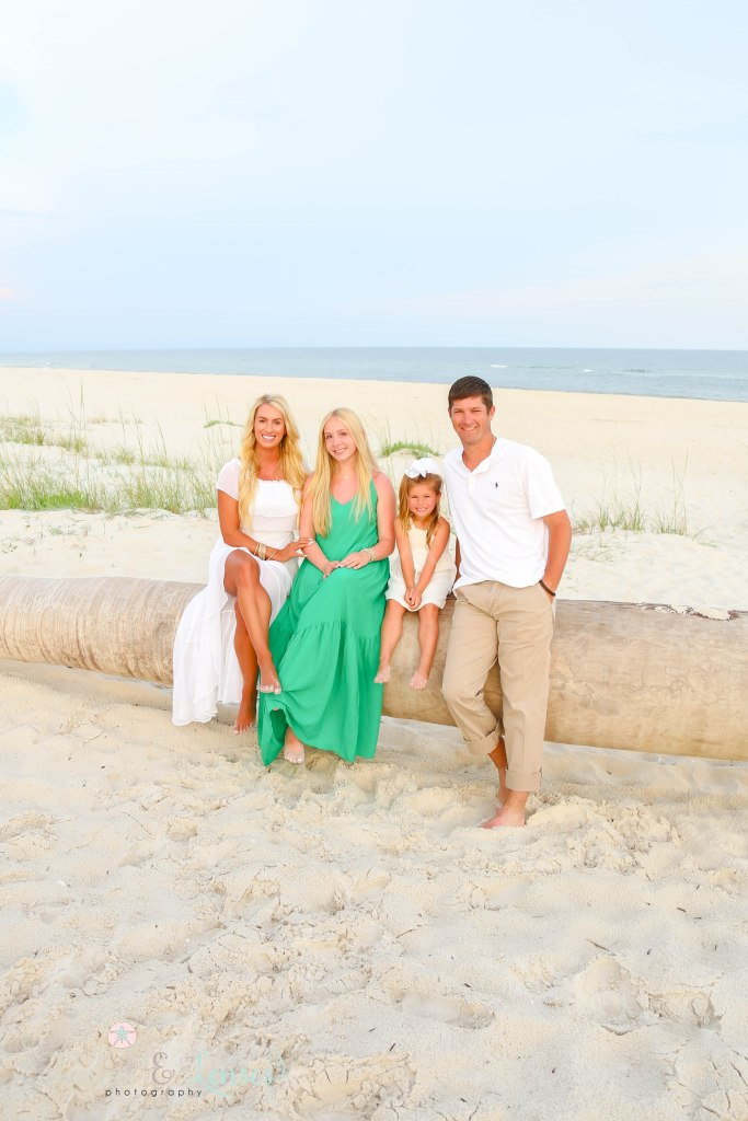 Mom and Dad sitting on a washed up palm tree on the beach with their teen daughter and young daughter at Johnsons Beach in Perdido Key Florida