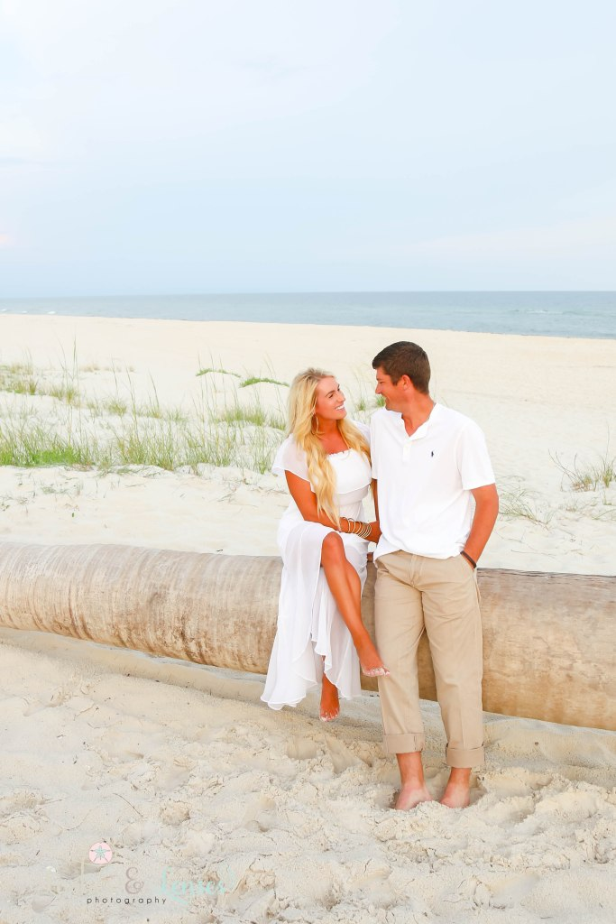 Wife and Husband sitting on a washed up palm tree on the beach and gazing into each others eyes at Johnsons Beach in Perdido Key Florida