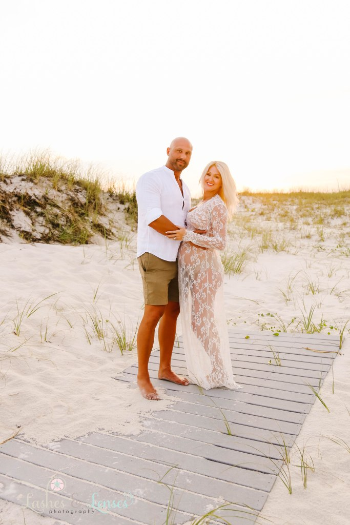 Husband holding pregnant wife's belly and standing on a washed up boardwalk on the beach at Johnsons Beach in Perdido Key Florida
