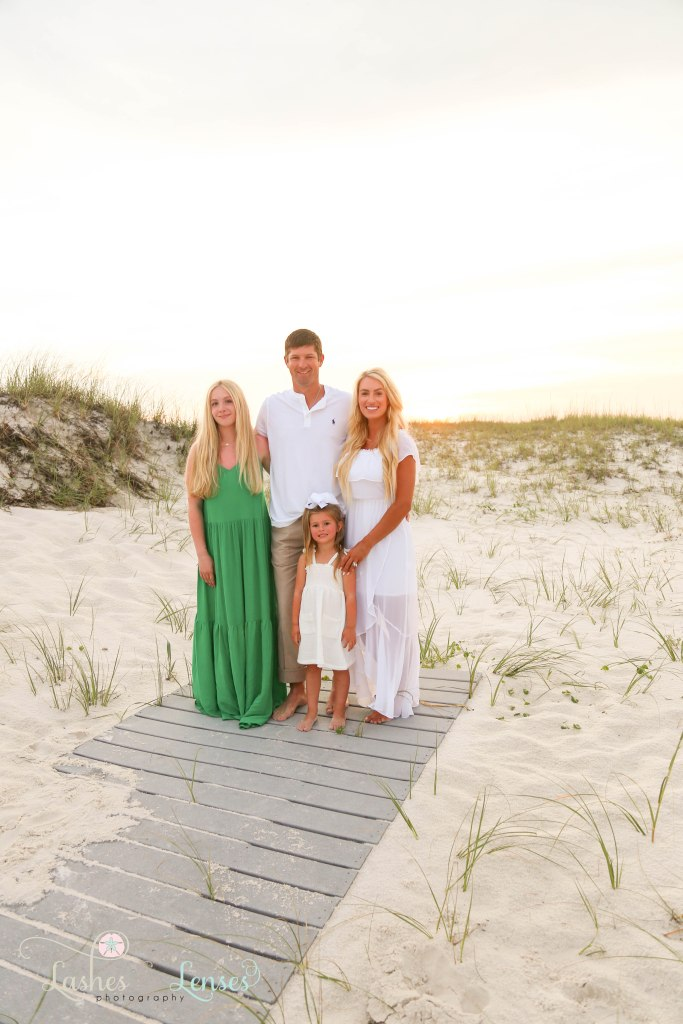 Family consisting of mom, dad, teen daughter and preschool age daughter standing on a washed up boardwalk at Johnsons Beach in Perdido Key Florida