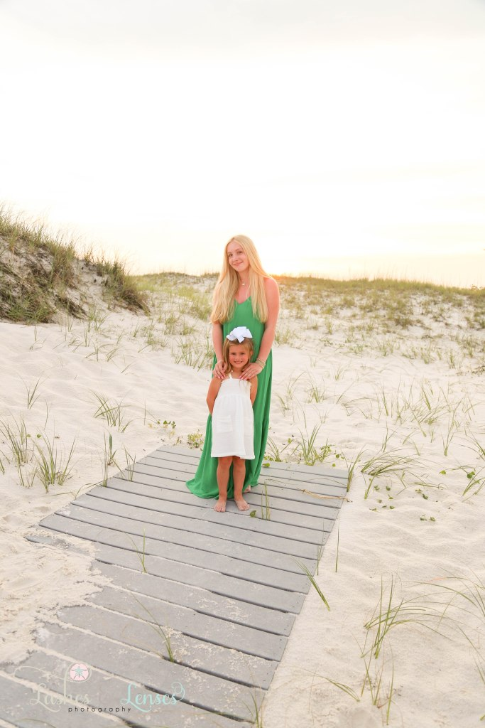 Older sister with her hands on younger sisters shoulders and standing on the boardwalk at Johnsons Beach in Perdido Key Florida