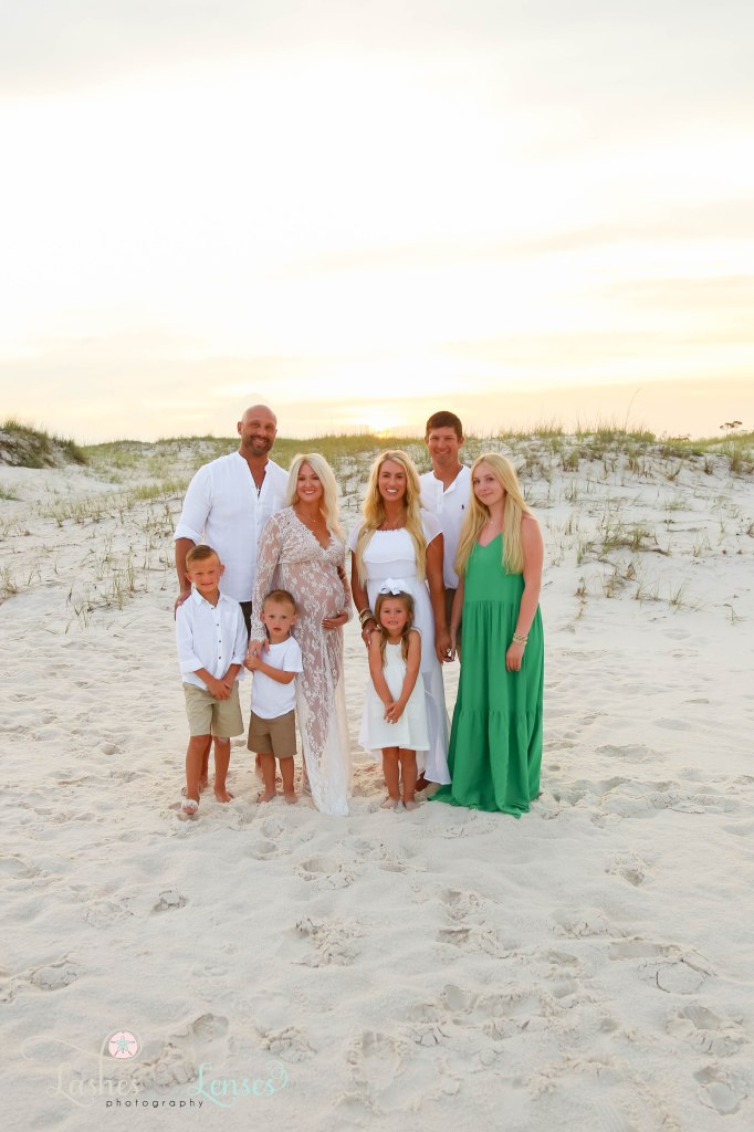 Two families standing on the beach with the sunset behind them at Johnsons Beach in Perdido Key Florida