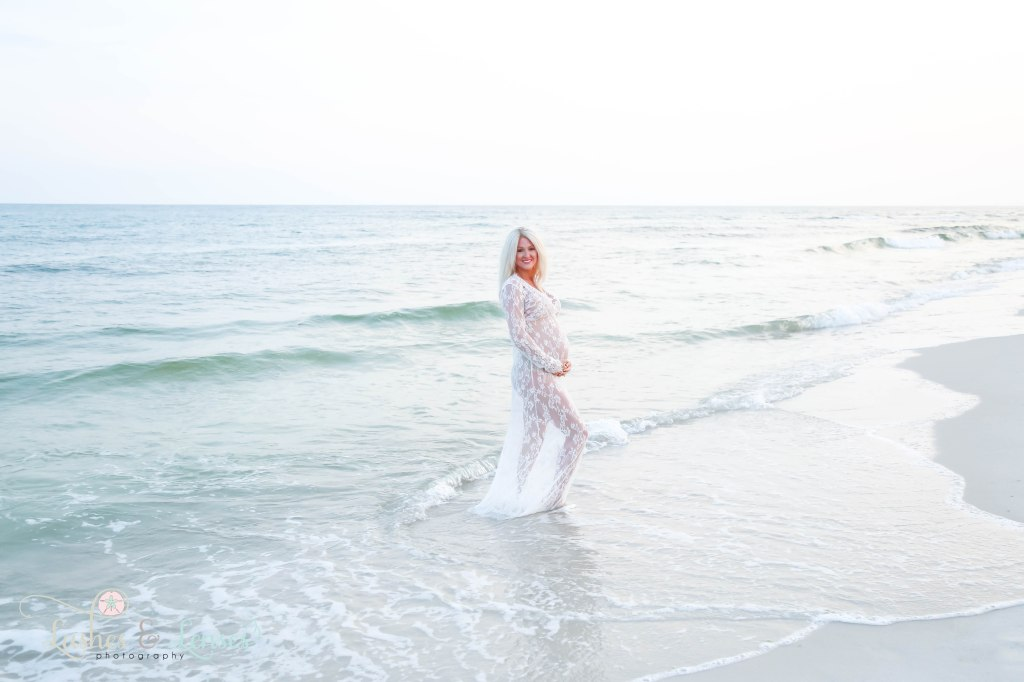 Pregnant woman in see through lace dress and standing in the waves of the gulf at Johnsons Beach in Perdido Key Florida