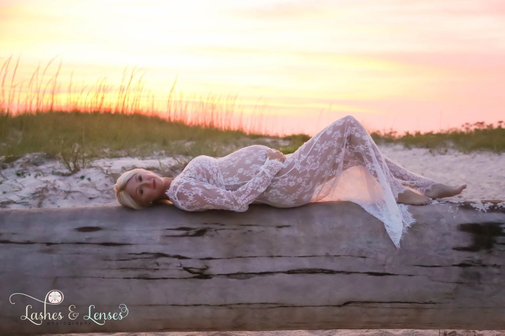 Pregnant woman laying on a washed up palm tree with the sunset behind her at Johnsons Beach in Perdido Key Florida