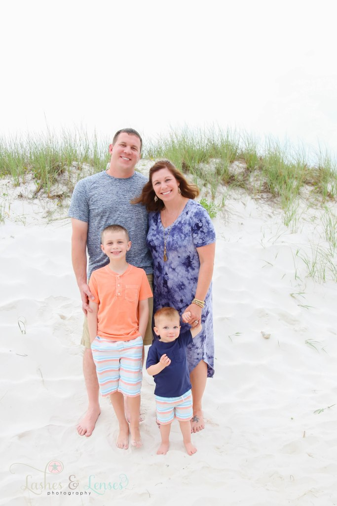 Mom and Dad with their two sons standing next to the sand dunes at Johnsons Beach in Perdido Key Florida