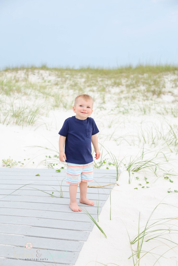 Toddler boy smiling big at the camera and standing on a boardwalk at Johnsons Beach in Perdido Key Florida